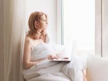Ungt nätt kvinnasammanträde på fönster med bärbara datorn och arbete arkivfoton