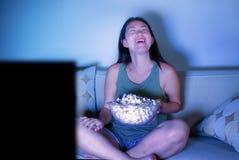 Ungt nätt och lyckligt asiatiskt koreanskt kvinnasammanträde på natten för show för komedi för television för vardagsrumsoffasoff arkivbild