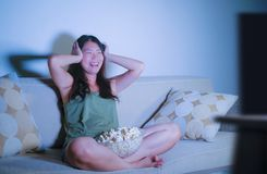 Ungt nätt och lyckligt asiatiskt koreanskt kvinnasammanträde på natten för show för komedi för television för vardagsrumsoffasoff royaltyfri fotografi
