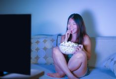 Ungt nätt och lyckligt asiatiskt koreanskt kvinnasammanträde på natten för show för komedi för television för vardagsrumsoffasoff royaltyfria foton