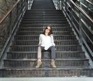 Ungt nätt stilfullt kvinnasammanträde på trappa Royaltyfria Bilder