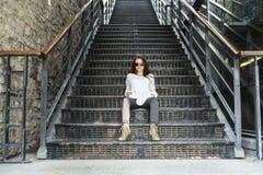 Ungt nätt stilfullt kvinnasammanträde på trappa Arkivfoton