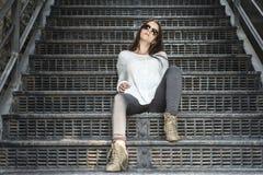 Ungt nätt stilfullt kvinnasammanträde på trappa Royaltyfri Bild