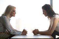 Ungt och gammalt sitta för affärskvinnor som är motsatt, utvecklingar kämpar på arbete arkivbild