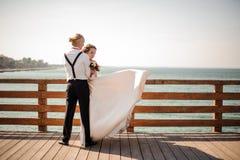 Ungt och härligt gift par som omfamnar på träbron i bakgrund av havet royaltyfria foton