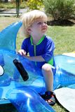 Ungt pojke- eller barnsammanträde på uppblåsbar delfin av simbassängen royaltyfri foto