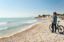 Ungt pojkeanseende bredvid en cykel på ett Pebble Beach som ser en piratkopieraslott Royaltyfria Bilder