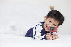 Ungt pojkeleende och lägga i sovrum litet barn som rymmer amer Royaltyfri Bild