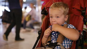 Ungt pojkesammanträde i en barnspårvagn i en flygplats stock video