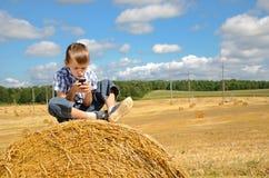 Ungt pojkesammanträde på höstack med telefonen Arkivfoto