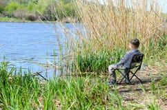Ungt pojkesammanträde på stol- och innehavmetspöet Fotografering för Bildbyråer