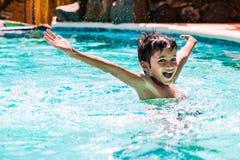 Ungt pojkeungebarn åtta år gammalt plaska i simbassängen som har öppna armar för rolig fritidsaktivitet Arkivfoton