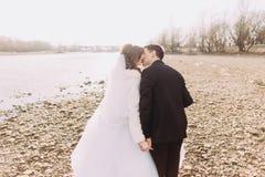 Ungt precis gift par som går tillbaka kyssa på flodkusten Royaltyfri Bild