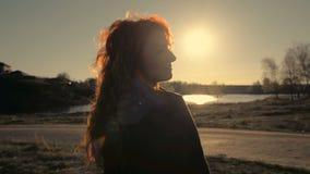 Ungt rödhårigt kvinnaanseende på bakgrunden av naturen tillbaka till kameran stock video