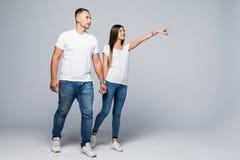 Ungt romantiskt gå för par som isoleras på grå bakgrund fotografering för bildbyråer