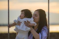 Ungt sött och lyckligt asiatiskt kinesiskt rymma för kvinna behandla som ett barn flickan som tillsammans svänger på strandgunga  royaltyfri foto