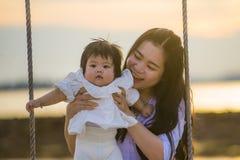 Ungt sött och lyckligt asiatiskt kinesiskt rymma för kvinna behandla som ett barn flickan som tillsammans svänger på strandgunga  royaltyfria bilder