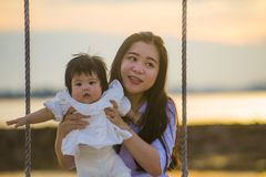 Ungt sött och lyckligt asiatiskt kinesiskt rymma för kvinna behandla som ett barn flickan som tillsammans svänger på strandgunga  arkivfoton