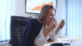 Ungt sammanträde för affärskvinna i kontoret och äta en hamburgare lager videofilmer