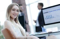 Ungt sammanträde för affärskvinna på ett skrivbord i kontoret royaltyfri foto