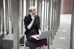 Ungt sammanträde för affärskvinna utanför med bärbar dator- och mobilphon royaltyfri bild
