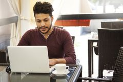 Ungt sammanträde för Blogger för affärsman på bärbara datorn, smartphonen och koppen arkivfoton