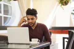 Ungt sammanträde för Blogger för affärsman på bärbara datorn, smartphonen och koppen royaltyfria bilder
