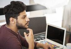 Ungt sammanträde för Blogger för affärsman på bärbara datorn, smartphonen och koppen royaltyfri bild