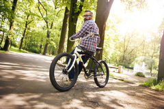 Ungt sammanträde för den moderna mannen på cykeln på parkerar att se bakom Arkivfoton