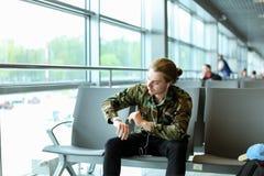 Ungt sammanträde för manlig person i väntande korridor på flygplatsen och att lyssna till musik med hörlurar och se klockan royaltyfri bild