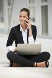 Ungt sammanträde för affärskvinna på trottoar genom att använda bärbara datorn, medan tala på telefonen Royaltyfri Fotografi