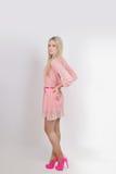 Ungt sexigt blont i rosa färgklänning studio vertikalt Royaltyfri Foto