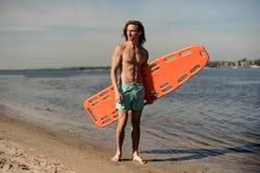 Ungt sexigt strandlivräddareanseende på sanden med liv-besparingen Royaltyfri Fotografi