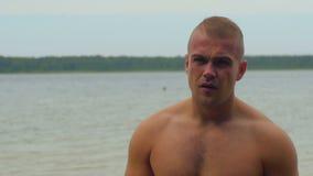 Ungt shirtless muskulöst stiligt mananseende på sjön i skog lager videofilmer