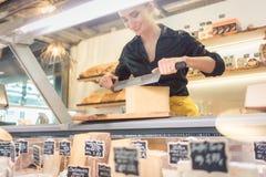 Ungt shoppa kontoristen i delikatessaffär som klipper ost arkivfoto
