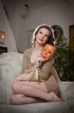 Ungt sinnligt kvinnasammanträde på soffan som rymmer en maskering Härlig lång hårflicka med bekväm kläder som dagdrömmer på soffa Fotografering för Bildbyråer