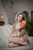 Ungt sinnligt kvinnasammanträde på soffan som rymmer en maskering Härlig lång hårflicka med bekväm kläder som dagdrömmer på soffa Royaltyfri Foto