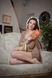 Ungt sinnligt kvinnasammanträde på soffan som rymmer en maskering Härlig lång hårflicka med bekväm kläder som dagdrömmer på soffa Royaltyfri Bild