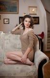 Ungt sinnligt kvinnasammanträde på att koppla av för soffa Härlig lång hårflicka med bekväm kläder som dagdrömmer på soffan, bara Royaltyfri Fotografi
