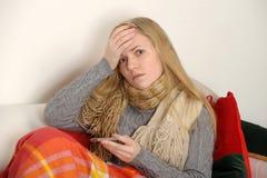 Ungt sjuk kvinnligt kontrollera henne förkroppsligar temperatu Arkivfoto