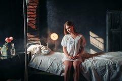 Ungt sjukt kvinnasammanträde på sjukhussäng på droppande royaltyfri fotografi