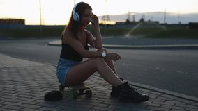 Ungt skateboarderkvinnasammanträde och sätter på hörlurar arkivfilmer