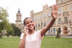 Ungt skolflickaanseende på skolgårdanswerinhpåringningen som vinkar till den gladlynta vännen arkivfoto