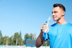 Ungt sportigt mandricksvatten från flaskan på stadion på solig dag fotografering för bildbyråer