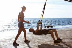 Ungt sportive folk som utbildar med trx nära havet i morgonen fotografering för bildbyråer