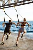Ungt sportive folk som utbildar med trx nära havet i morgonen arkivfoton