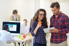 Ungt startup affärsfolk, par som arbetar på minnestavladatoren Fotografering för Bildbyråer