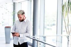 Ungt stilfullt affärsmanUsing Smartphone At avbrott Royaltyfri Bild