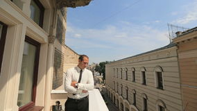Ungt stiligt affärsmananseende på balkongen och kontrolleratid på hans klocka lager videofilmer