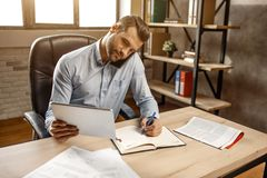 Ungt stiligt affärsmanarbete i hans eget kontor Han sitter på tabellen och samtalet på telefonen Också grabbhandstil i dokument arkivfoto
